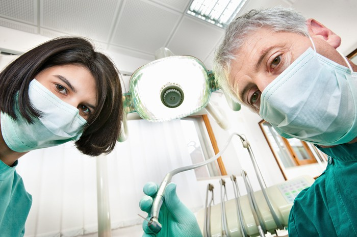 a dentist and his assistant looking into a camera