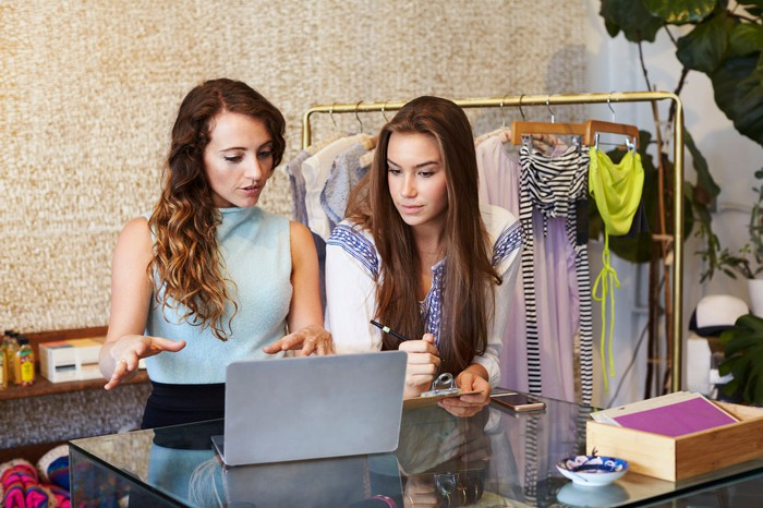 Two young women are working in a clothing store.