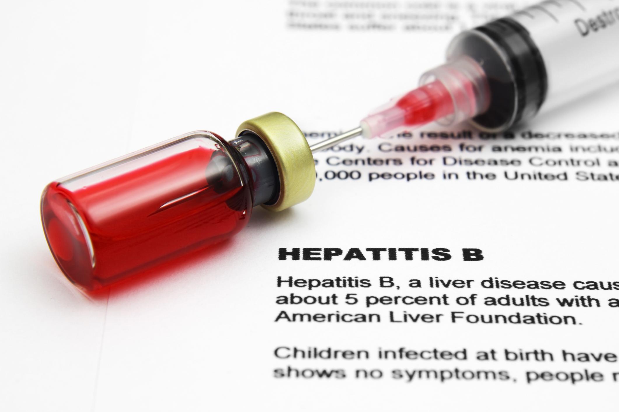 Syringe and vial on top of hepatitis B document