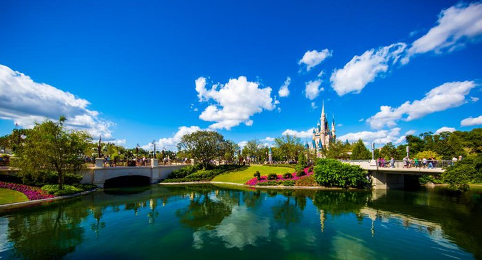 An outside view including a lake and green land at a Disney theme park.