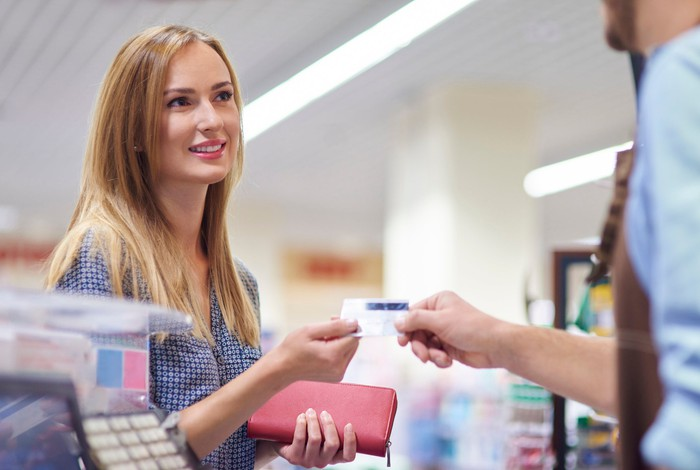 A woman hands over her credit card at retail checkout.