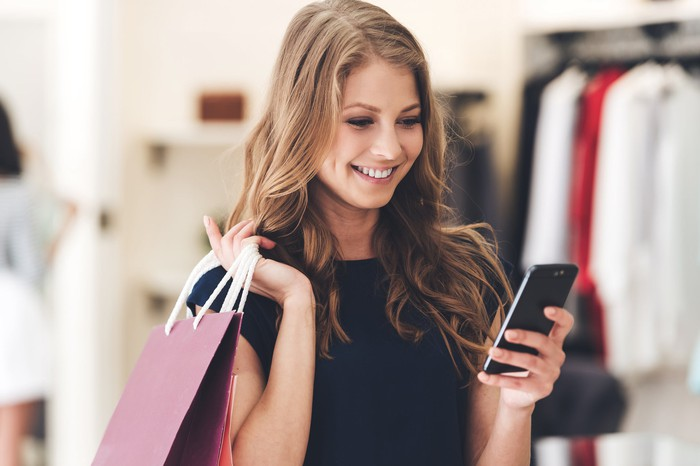 A woman holds a shopping bag and smiles while looking at her smartphone