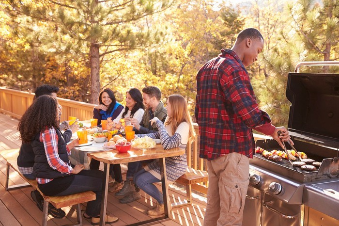 Friends having a barbecue on an outdoor deck.