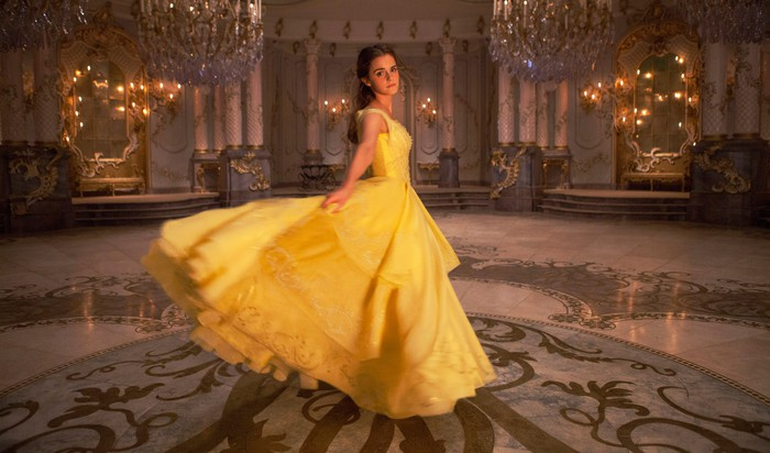 """Emma Watson as Belle in a yellow gown in a ballroom for """"Beauty and the Beast"""" movie."""