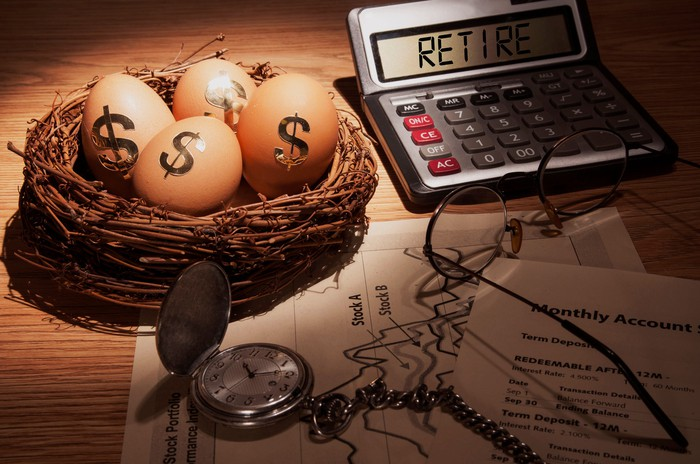 A bird nest with eggs bearing dollar signs, next to a calculator that says retire and a stopwatch.
