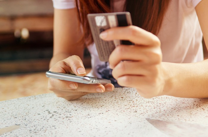 A person holding a smartphone in one hand and a credit card in the other.