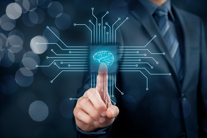 A man in business suit pressing a screen with an image of a human brain at the center of a semiconductor -- concept for artificial intelligence.
