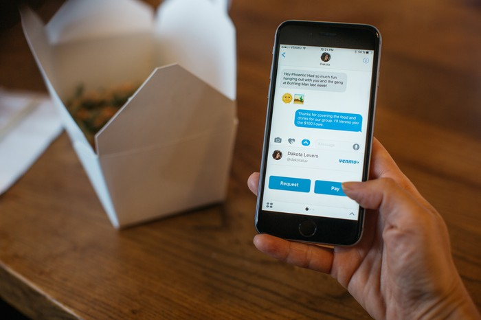 Smartphone being held showing Venmo app with Chinese food container on table in background.