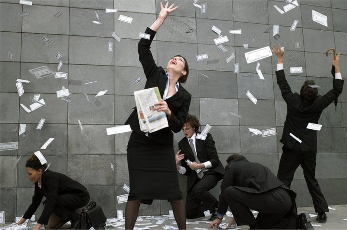 Cash money raining down on happy people in business attire.