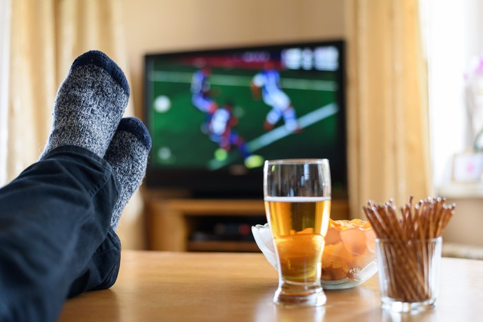 Drinks and snacks sit on a coffee table while a viewer watches a soccer match on TV.