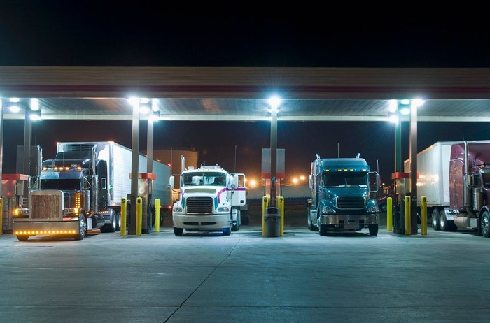 Semi trucks refueling at a truck stop.