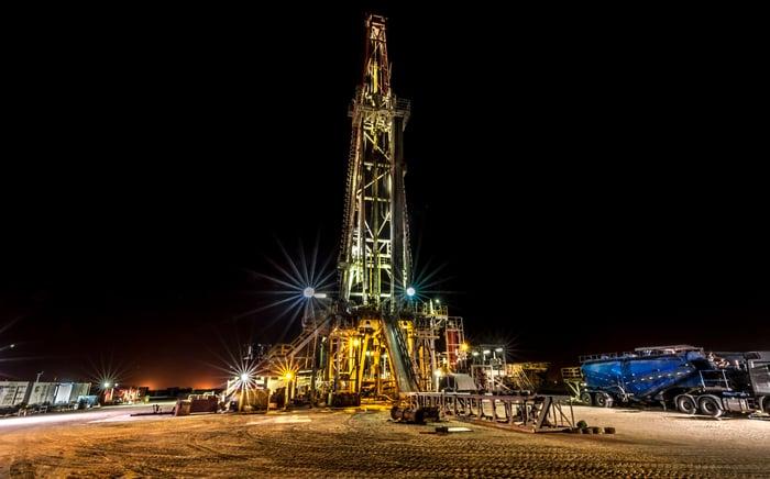 An illuminated drilling rig at night