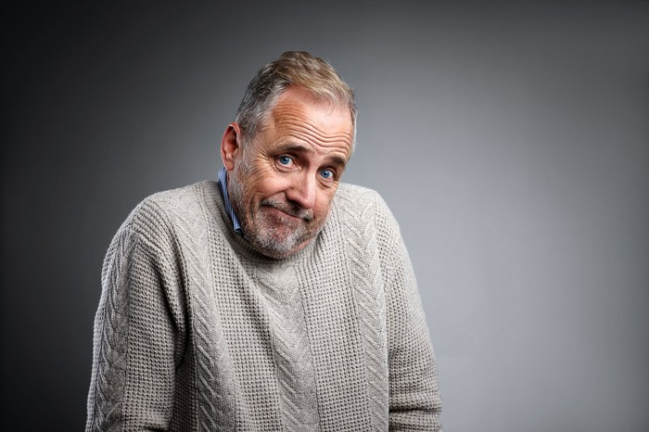 An elderly man shrugging his shoulders while smirking.