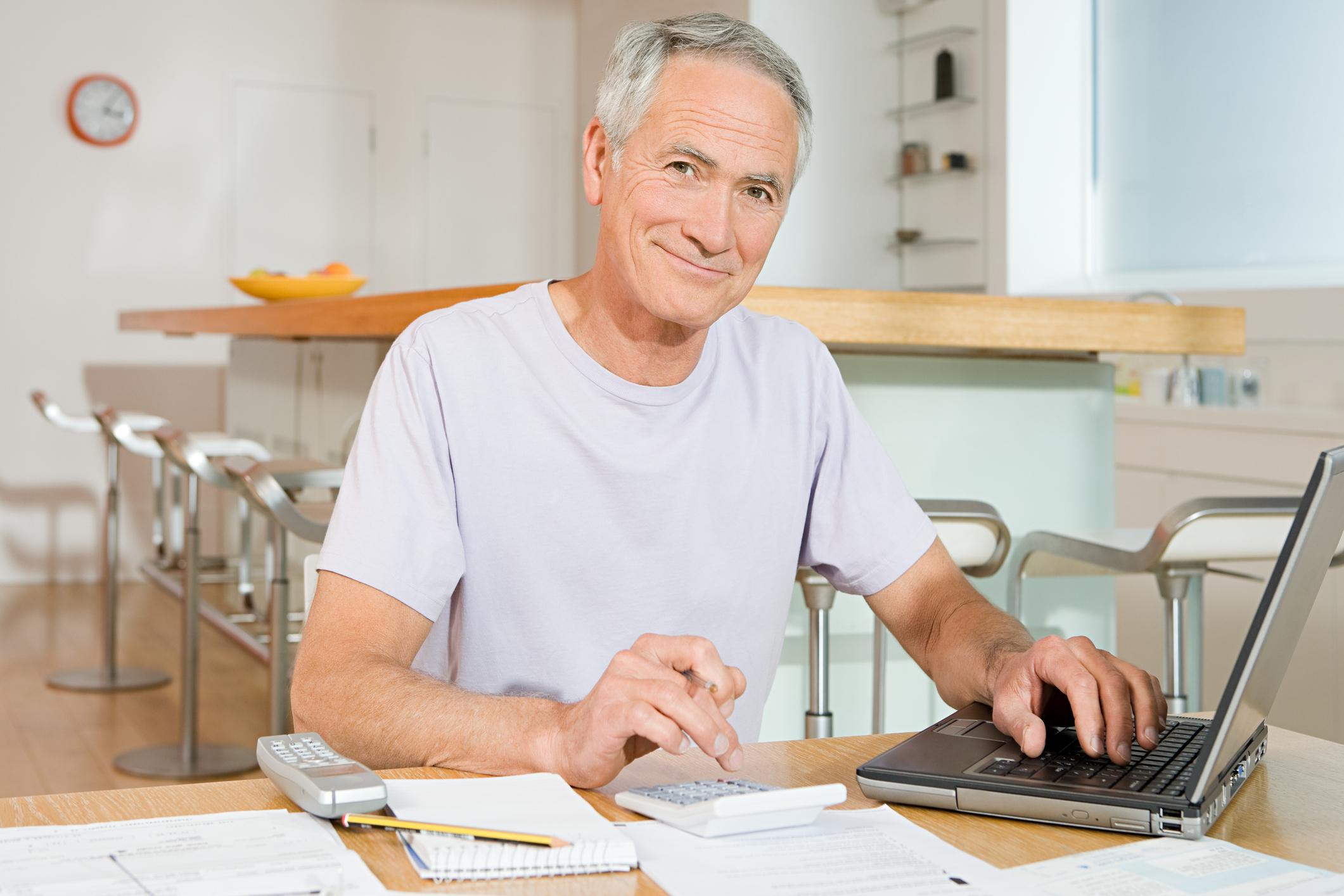 A senior man using his laptop to examine his finances.