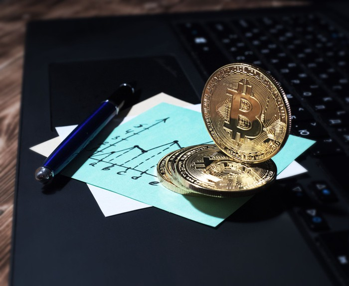 A golden physical bitcoin on top of a laptop, next to a business graph and pen.