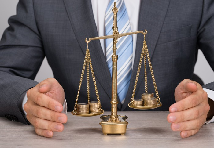 business man weighs coins on two sides of a suspension scale.