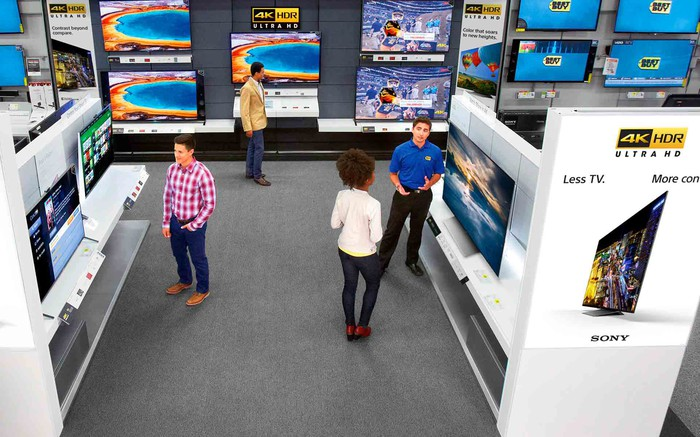 Best Buy televisions at the store with customers talking to a Best Buy salesperson.