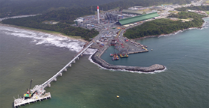 Production facility on a coast line with a shipping pier and dock extending into the water.