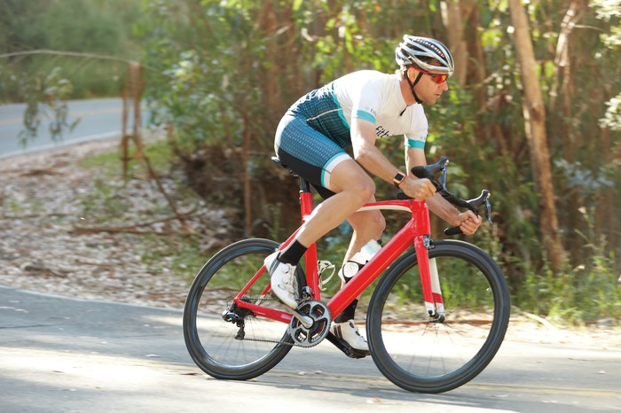 Biker dressed in Fitbit biking uniform riding downhill with Fitbit Ionic on his wrist.