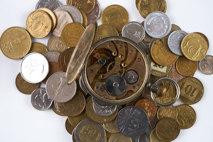 A clock with the complicated clockwork exposed, on top of a pile of coins.