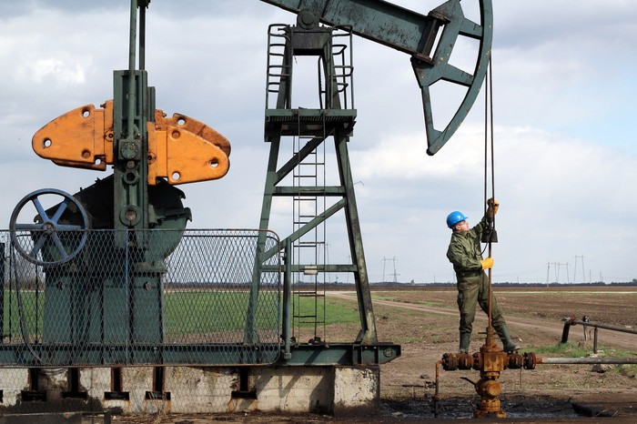 Oil field worker standing on a pump jack.
