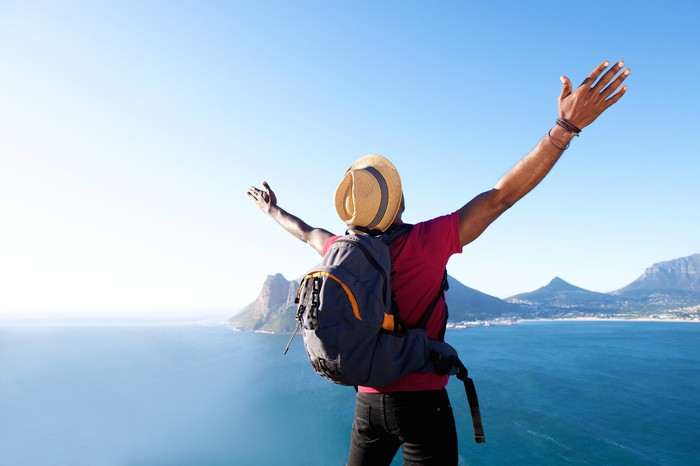 Man with backpack facing ocean and mountain scenery