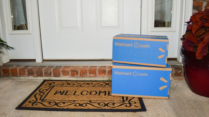 Two Walmart boxes stacked on a welcome mat