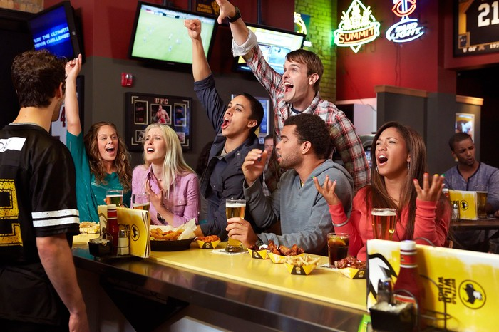 Patrons cheering a sporting event at Buffalo Wild Wings