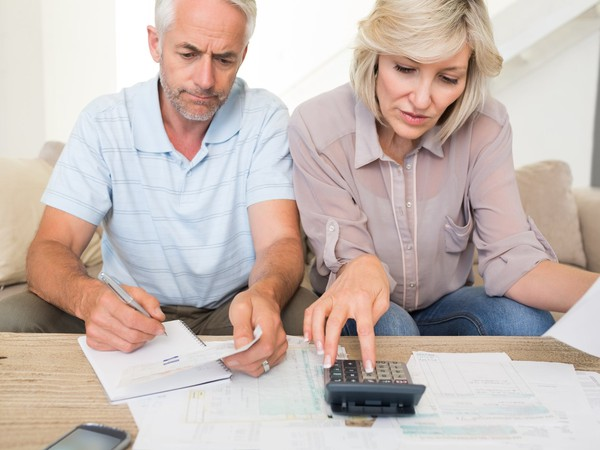mature couple looking at documents and using calculator bills finances