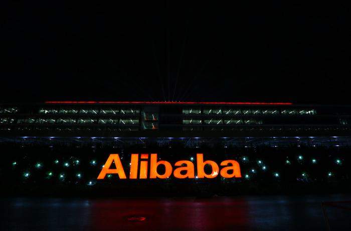 The word Alibaba lit up in orange in a nighttime photo of Alibaba's offices in China