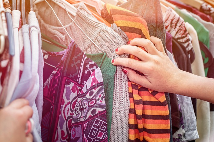 A woman's hand leafs through a rack of clothes.