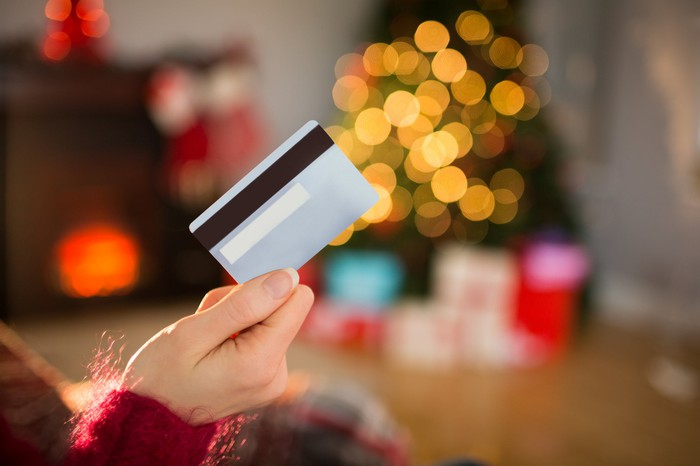 A person holds a credit card in the air in front of a Christmas tree surrounded by presents.