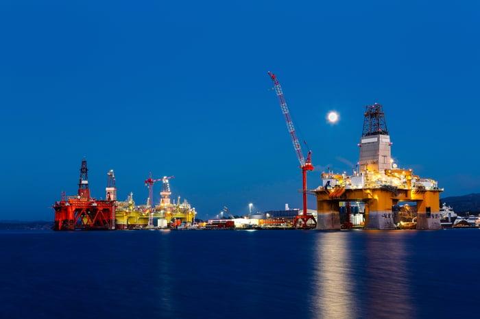 Multiple drilling rigs docked at night.