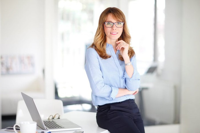 A female dressed in business attire leaning on a desk and looking at the camera.