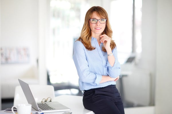 Confident Female Executive Leaning on Desk