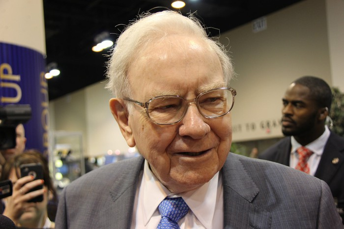 Warren Buffett speaking to a group of people at a convention.