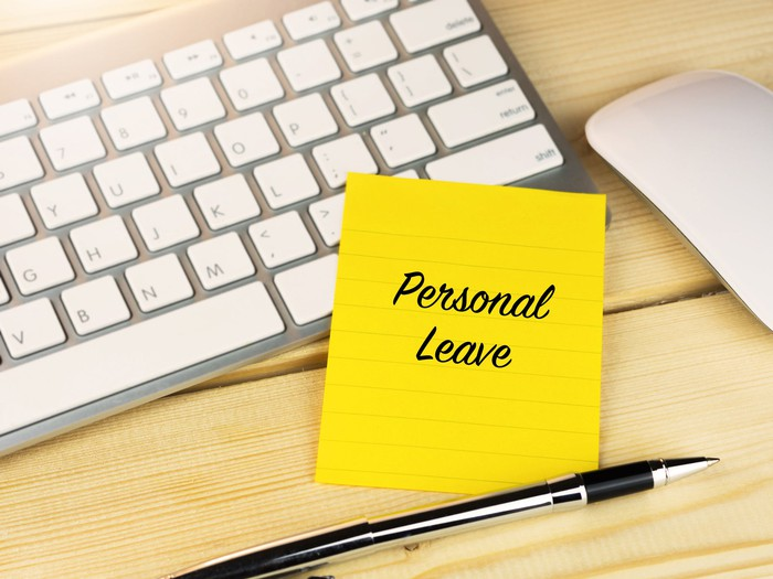 Post-it note that says personal leave on a keyboard