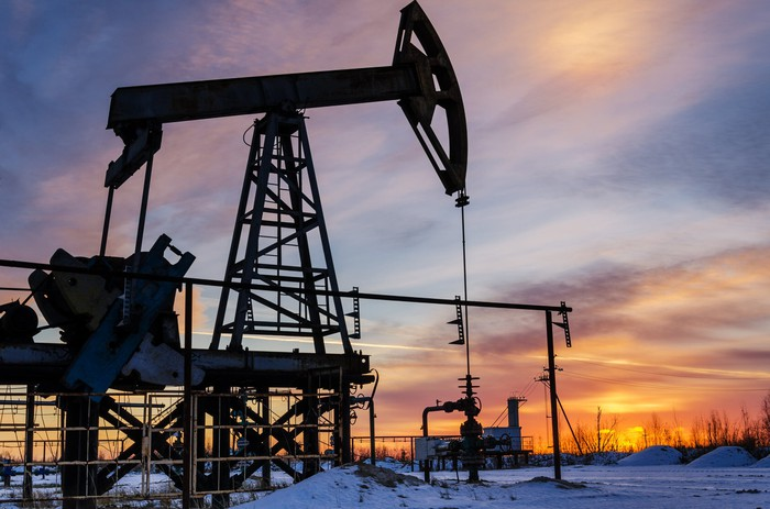 An oil pump with the sun in the background and snow on the ground.