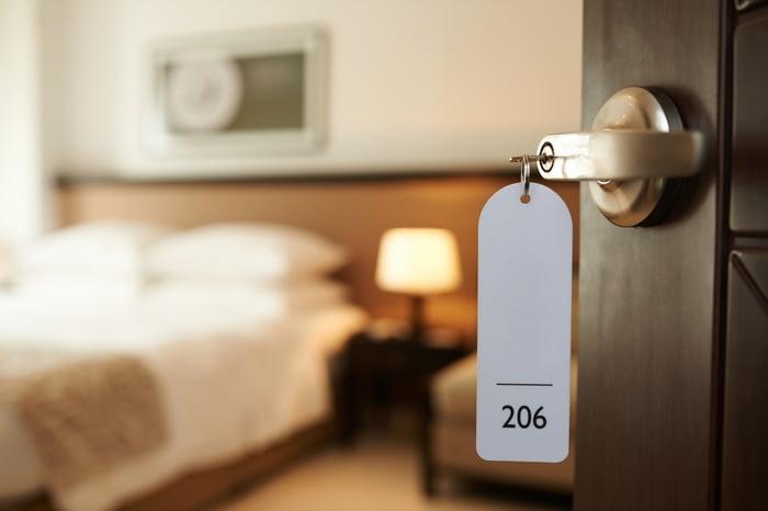 Hotel room door open, with key inserted in lock.