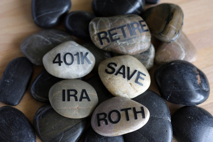 smooth stones on which are written save, retire, roth, ira, 401k