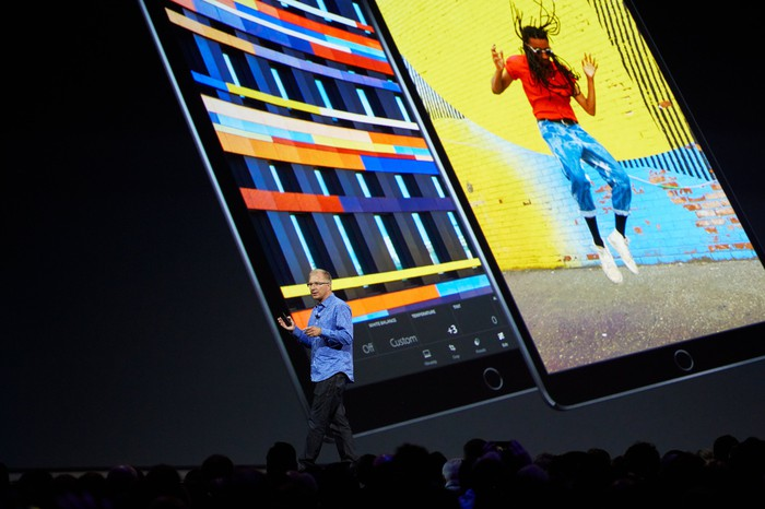 Apple executive Greg Joswiak on stage with images of the 10.5-inch iPad Pro projected on the screen behind him.