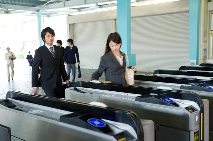 Two young Japanese women in business attire cross through a train-station turnstile.