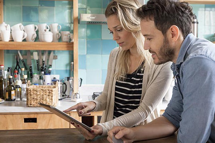 Man and woman in kitchen (cups and bottles on a shelf in background) looking at a tablet and discussing something.
