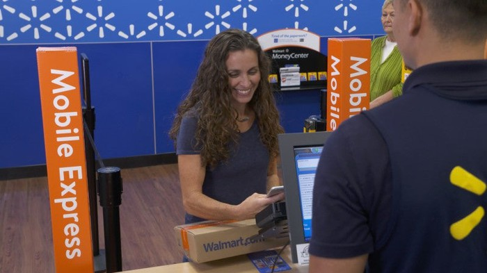 A Walmart customer scans an item at the Mobile Express counter