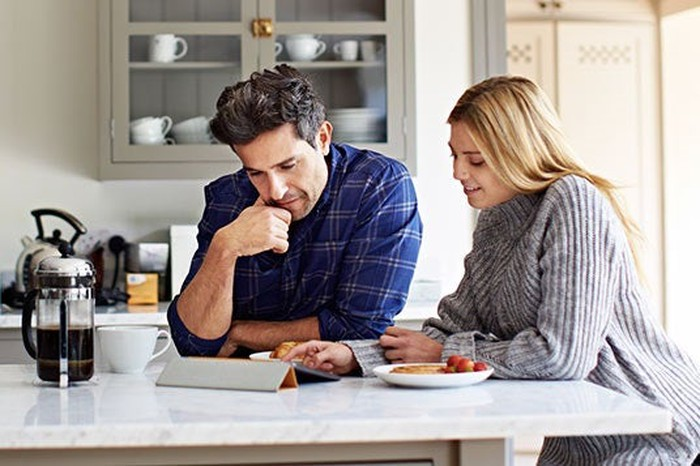 Couple sitting at table peering at tablet, some berries and a coffee maker in front of them.