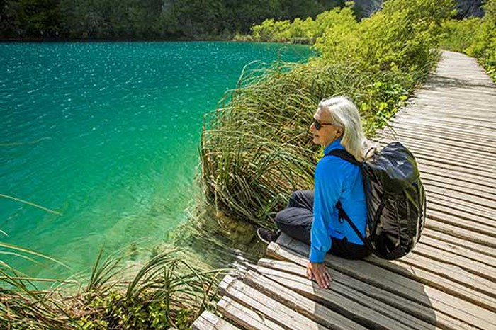 Older woman with backpack sitting on wodden pathway overlooking blue-green water.