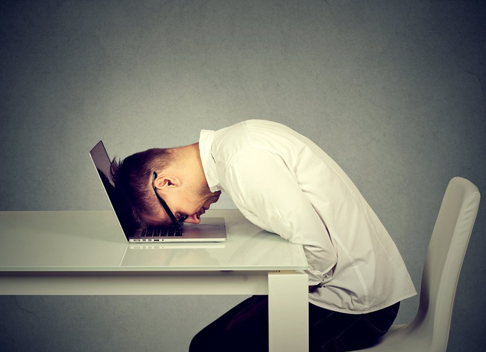 Man resting his head against a laptop