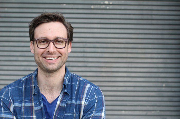 Smiling man with glasses in plaid shirt
