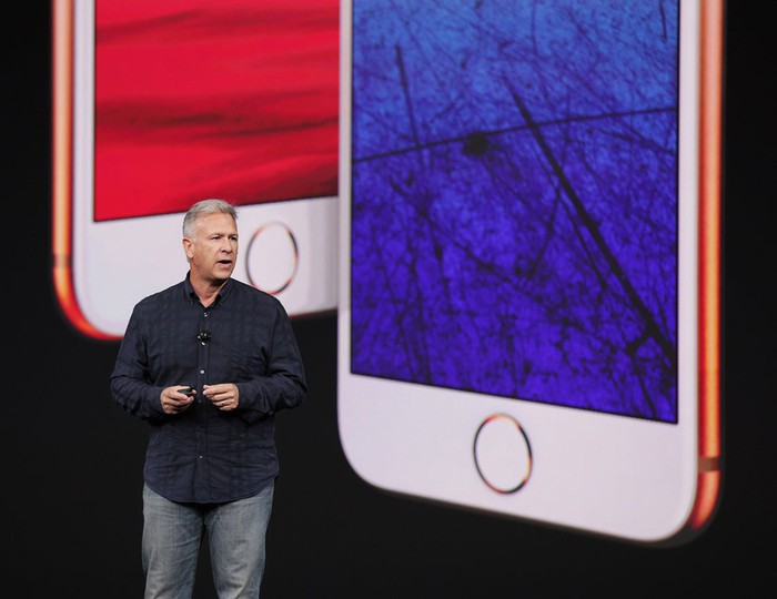 Apple executive Phil Schiller on stage with the iPhone 8 and iPhone 8 Plus projected on the screen behind him.