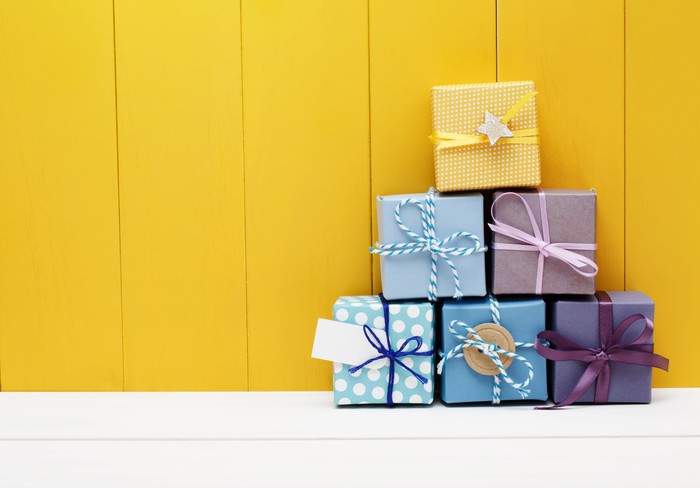 Six wrapped presents stacked in a pyramid shape against a yellow wall.